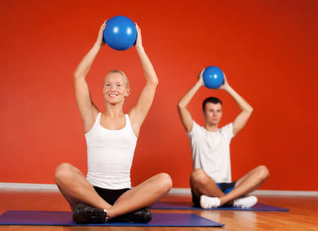 Group of people doing stretching exercise with fitness balls photo