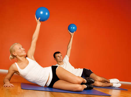 Group of people doing stretching exercise with fitness balls in fitness room photo