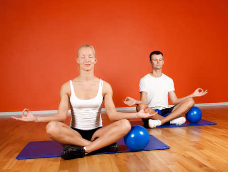Group of people doing yoga exercise with fitness balls in gym room photo