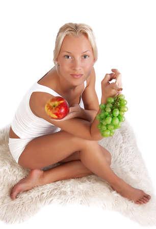 sexy girl sitting: Ritratto di sexy ragazza seduta sul � sceso con uva e mela in mano