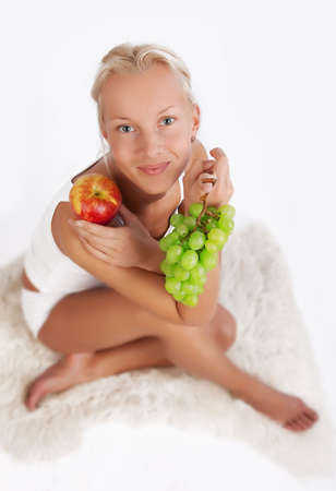 Portrait of sexy woman sitting with grapes and apple sitting on fell photo