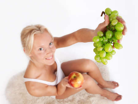 Close-up of green grapes in hands of blond girl, who is sitting on fell photo
