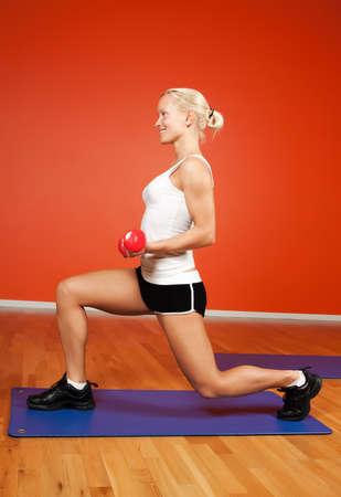 Beautiful blond athlete making exercise with dumbbells photo