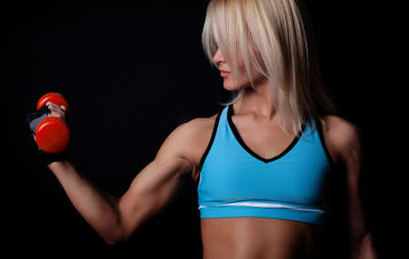 dark blond: Portrait of a sportswoman lifting heavy dumbbells in dark gym room Stock Photo