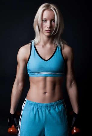 Portrait of tired sexy blond athlete  in dark gym room