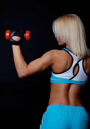 Portrait of a sportswoman lifting heavy dumbbells from behind