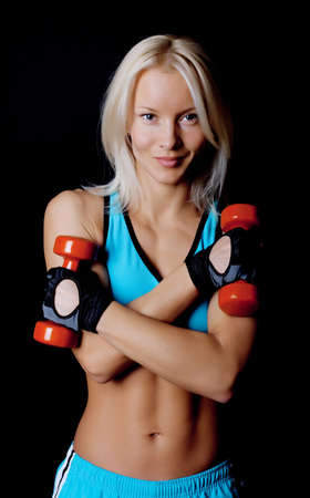 Portrait of a sexy athlete holding dumbbells in gym room