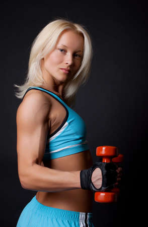Portrait of a athlete lifting dumbbells in gym room