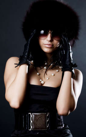 Stylish girl wearing fur cap and leather gloves photo