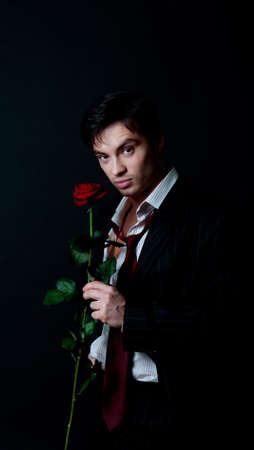 Portrait of handsome man wearing suit and  holding rose photo