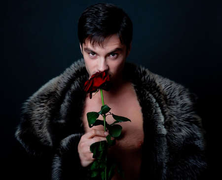manteau de fourrure: Image du m�le attrayant holding et odeur rouge rose Banque d'images