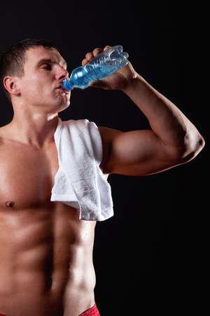 Portrait of muscular sportsman drinking water