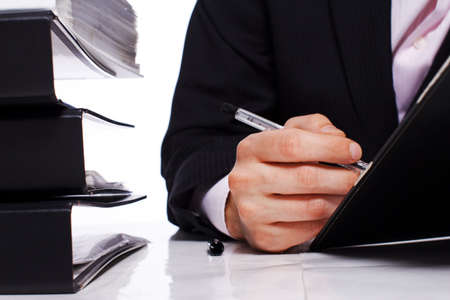 Close up of businessman hand writing with some folders on a table Stock Photo