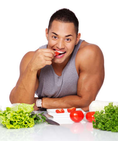 Portrait of sexy man eating on the kitchen