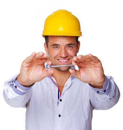 Portrait of smiling engineer posing in studio in helmet with key Stock Photo - 17752883