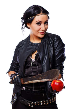 Portrait of sexy brunet posing in studio with machete and apple photo
