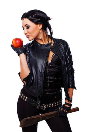 Portrait of sexy brunet posing in studio with machete and apple