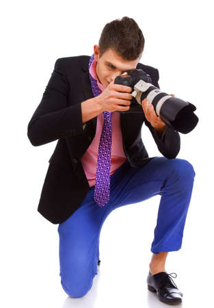 A handsome photograph is taking a picture while kneeling photo