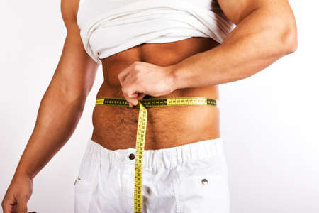 Muscular and tanned man is being measured  Stock Photo