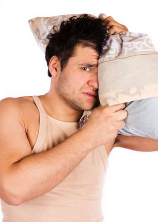 A tired looking man. He is holding a pillow  Stock Photo - 18208295