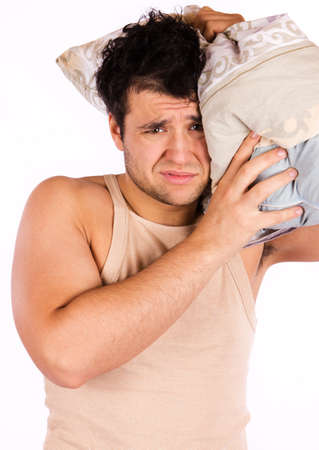 A tired looking man. He is holding a pillow  photo