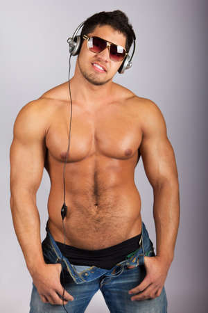 hombre desnudo: hombre guapo escuchando m�sica en los auriculares contra fondo natural