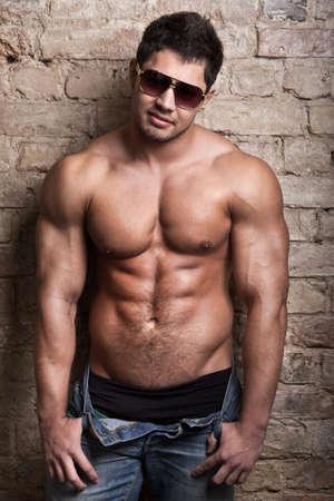 gay men: Retrato de un hombre musculoso posando frente a la antigua muralla
