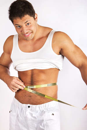 measured: Muscular and tanned man is being measured  Stock Photo
