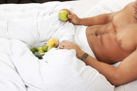 portrait of attractive young man with fruits in his bed   Stock Photo - 18255548