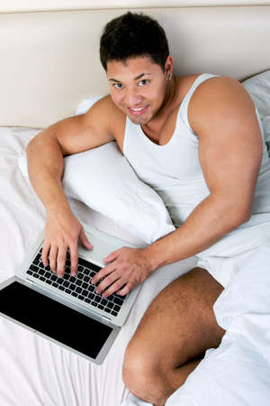 Young man using laptop at the bedtime Stock Photo - 18300441