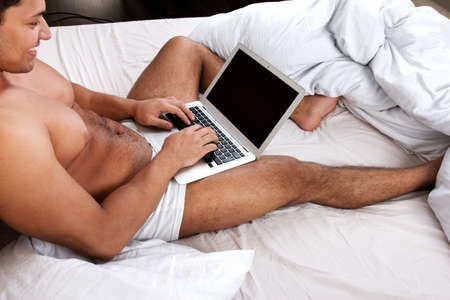 Young man using laptop at the bedtime Stock Photo - 18300461