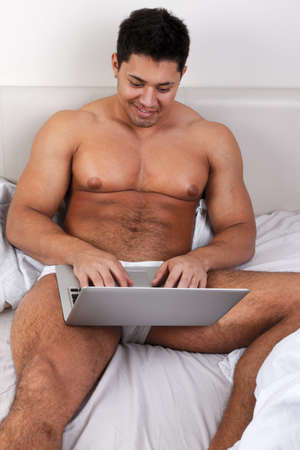 Young man using laptop at the bedtime