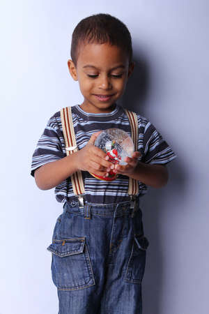 3 year old: Cute happy 3 year old American-African boy playing with christmas ball Stock Photo