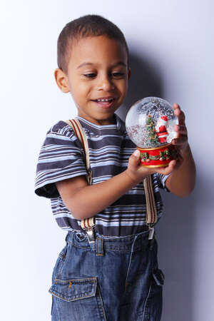 Cute happy 3 year old American-African boy playing with christmas ball photo