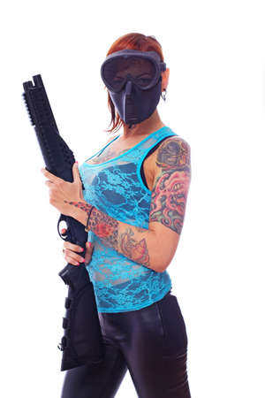 A young masked punk girl is firmly holding her shotgun photo