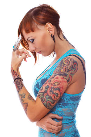 Portrait of a tattooed girl wearing a metal finger nail. photo