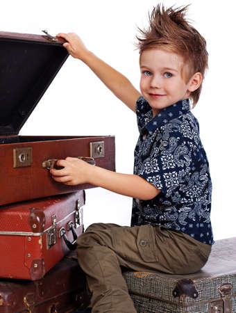 Portrait of young traveler posing in studio with suitcase photo