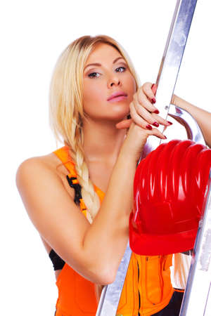 Portrait of sexy blonde worker posing in studio in red helmet near ladder photo