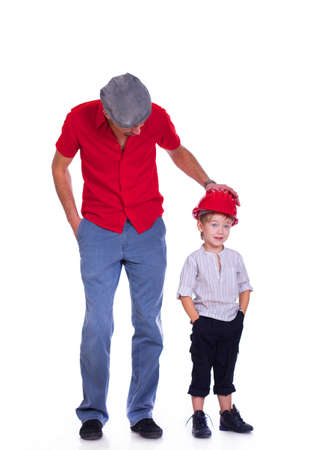 Portrait of son and father posing in studio in red helmet photo