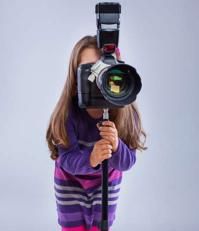 A small cute kid is toying with a camera
