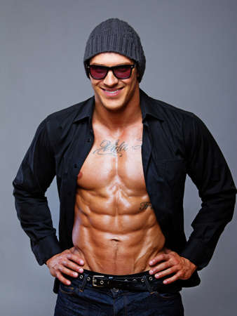 Photo of a hot male wearing some tidy clothes and demonstrating his gorgeous abs