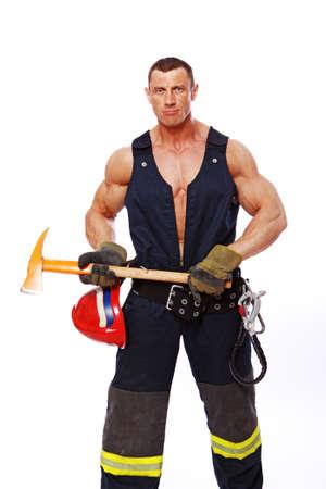 Portrait of muscle fireman posing in studio in uniform photo