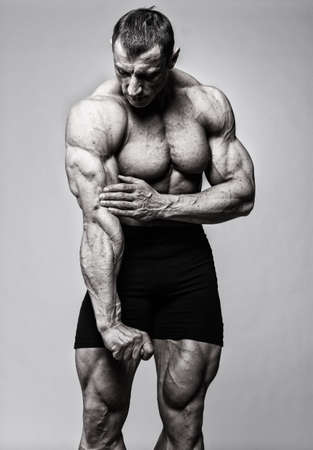weight training: Portrait of muscle man posing in studio