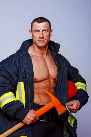 Portrait of muscle fireman posing in studio in uniform photo