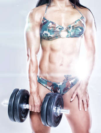 Portrait of strong and beautiful woman with muscles photo