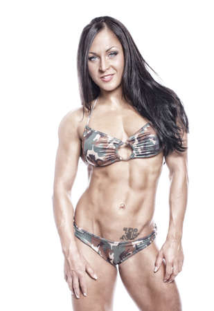 Portrait of strong and beautiful woman with muscles