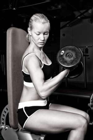 Portrait of a blond sportswoman lifting heavy dumbbells in empty dark gym room photo