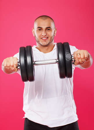 Portrait of sexy man posing in studio with dumbbells photo