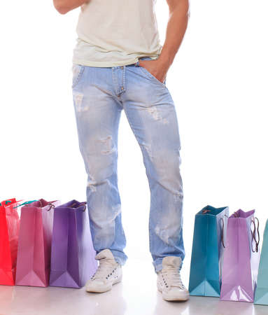 Young fashionable guy with shopping bags over a white photo