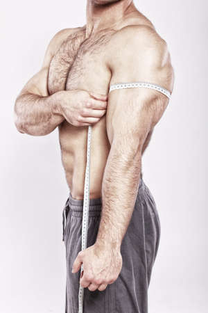 nude male: Close up of man measuring his arm biceps Stock Photo